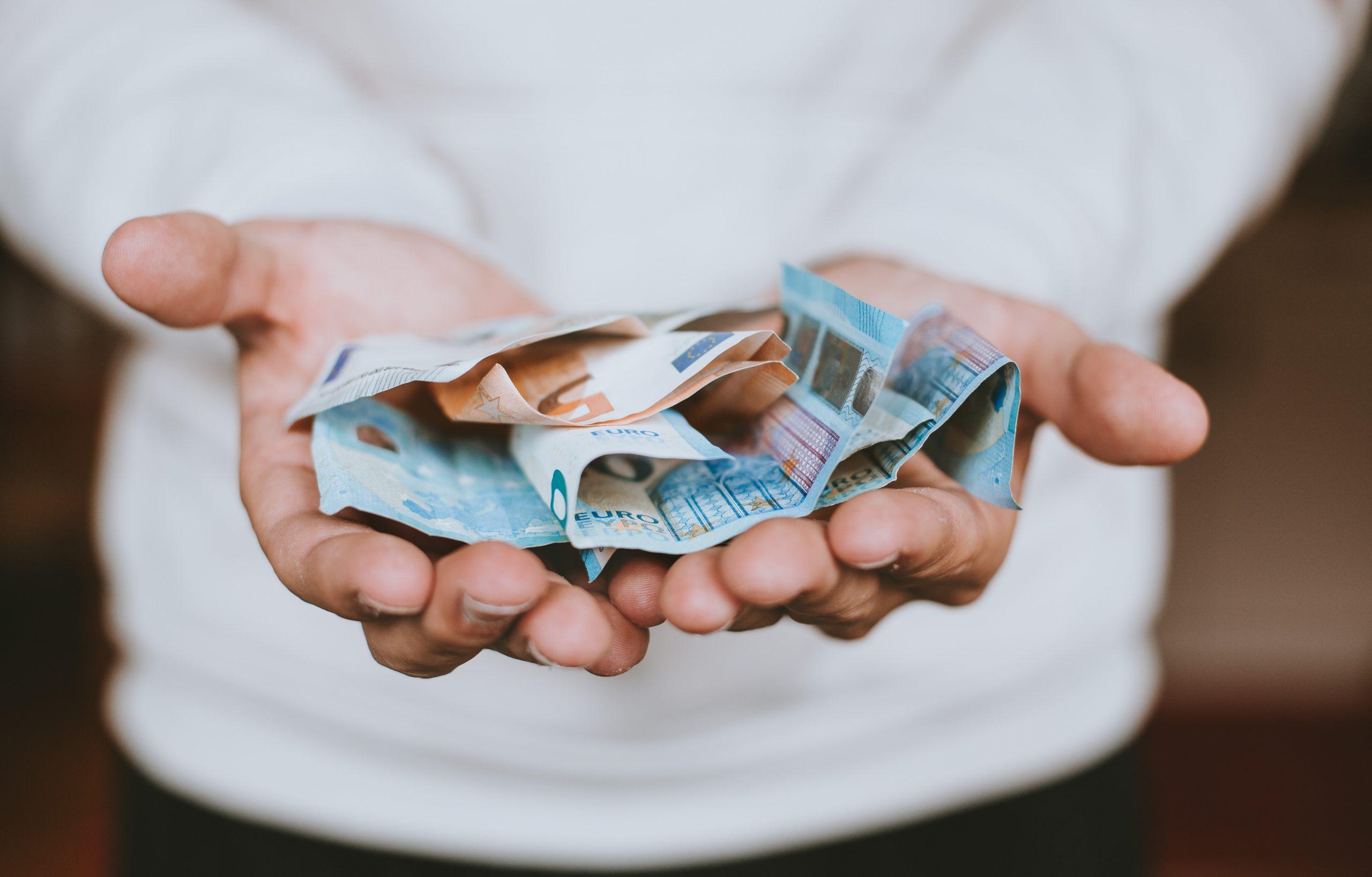Locataire qui tend des billets pour payer son loyer